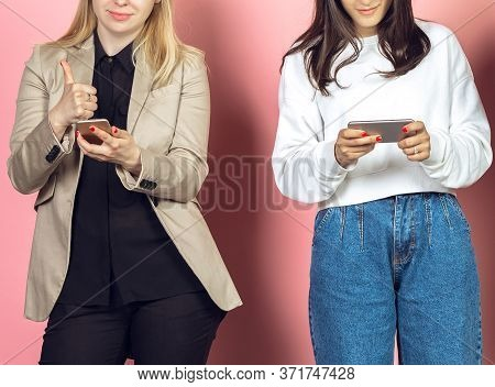 Two Girls, Friends Using Mobile Smartphones. Teenagers Addiction To New Technology Trends. Close Up.