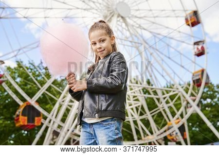 Portrait Of A Child With Sweet Cotton Candy. A Little Girl On The Background Of Ferris Wheel Is Eati