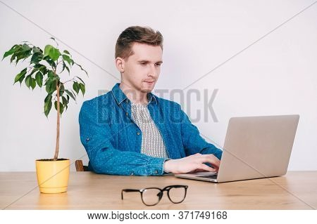Young Man In Shirt And Glasses Working On Laptop Computer Sitting At The Table On A White Background