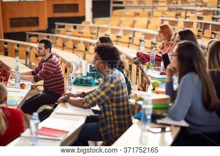 Young students focused on lecture in amphitheater