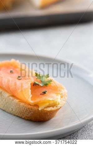 Bruschetta With Smoked Salmon And Butter On Concrete Background. Delicious Snack Or Appetizer.close