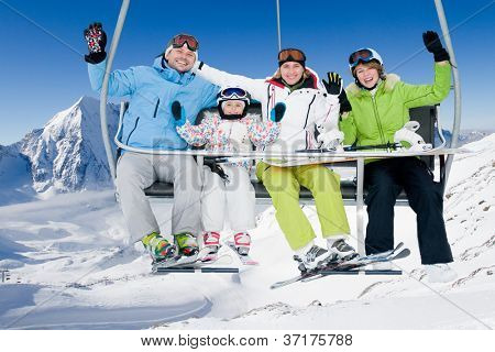 Skiing, winter - happy family ski team on ski lift
