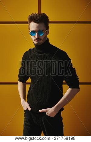 Urban style. Profile portrait of a stylish young man in black pullover and round mirror sunglasses standing on a street by the yellow industrial wall. Male fashion. Copy space.