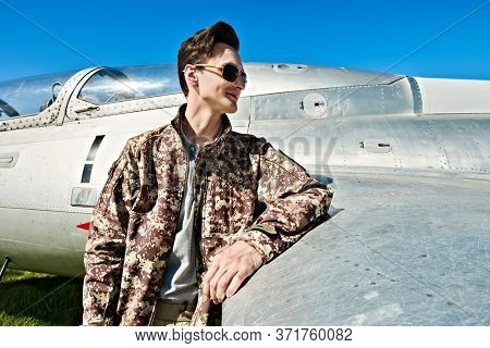 Handsome man pilot wearing military uniform standing next to his fighter plane at the airfield. Military aircraft.