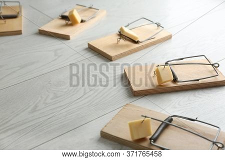 Mousetraps With Pieces Of Cheese On White Wooden Background. Pest Control