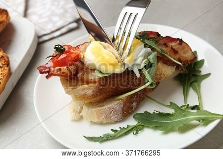 Cutting Tasty Egg Benedict On Plate, Closeup