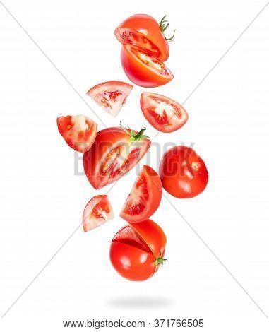Whole And Sliced Fresh Tomatoes Fall Down On A White Background