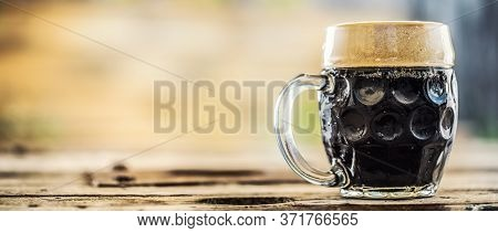 Pint Of Dark Beer On A Wooden Table Placed On The Side Of A Photograph.