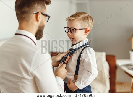Back View Of Young Man In Formal Wear And Eyeglasses Adjusting Necktie Of Cheerful Little Kid In Sim