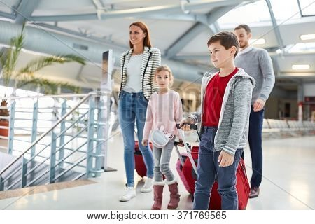 Family with children in the airport terminal when transferring or on arrival