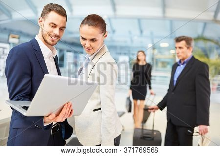 Business people in the airport with laptop computer reading news before their business trip