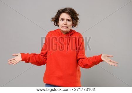 Puzzled Perplexed Young Brunette Woman Girl In Casual Red Hoodie Posing Isolated On Grey Wall Backgr