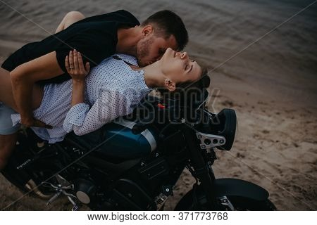 Couple Makes Love On Beach Lying On Motorcycle On Water Background. Closeup.