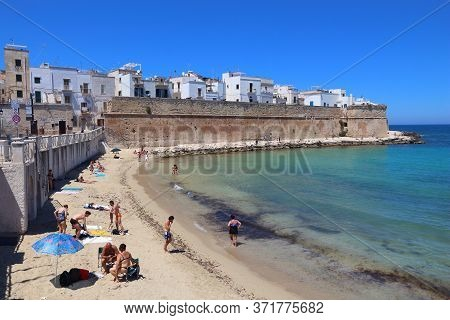 Monopoli, Italy - May 29, 2017: People Visit Monopoli Beach In Apulia, Italy. With 50.7 Million Annu