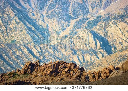 Boulders And Rocks With The Rugged Sierra Nevada Mountains Beyond Taken At The Alabama Hills Near Lo