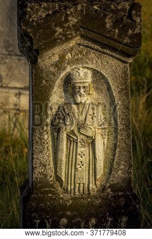 Ancient Stone Statue On Gothic Graves At Cemetery In Brody, Ukraine. An Old Abandoned Overgrown Ceme
