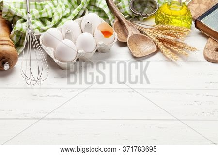 Cooking utensils and ingredients on wooden background. With copy space for your recipe