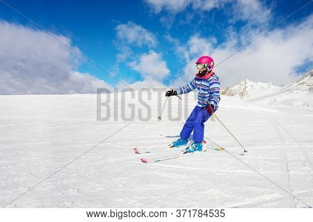 Alpine Ski Portrait Of A Girl In Colorful Sport Outfit Going Downhill
