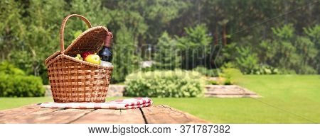 Picnic Basket With Fruits, Bottle Of Wine And Checkered Blanket On Wooden Table In Garden, Space For