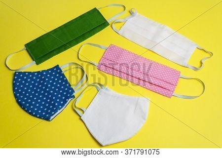 Five Colored Different Reusable Medical Masks On Yellow Isolated Background. Hygienic Antimicrobial,
