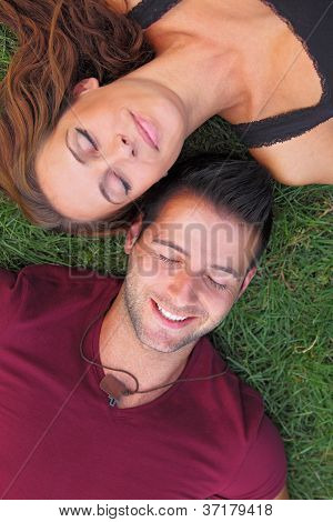 Close-up portrait of a couple lying on the grass