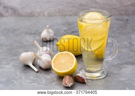 Therapeutic Drink Of Lemon And Garlic In A Glass On The Table. Alternative Medicine, Treatment With