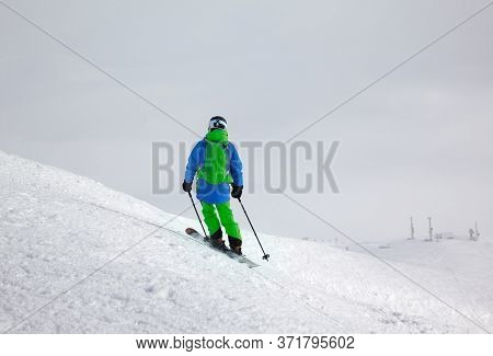 Skier Before Downhill On Freeride Slope And Overcast Misty Sky At Day With Bad Weather Before Blizza