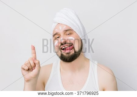 Funny Bearded Man With White Towel On His Head Showing His Finger With Face Cream On It, Smears A Cr