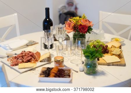 Holiday Decoration On Table. Floral Arrangement With Cheese Appetizer, Fruits And Wine.