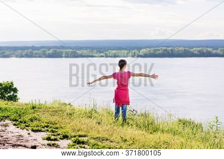 Local Travel. Girl On An Elevated Bank Of The River With Arms Outstretched. Summer Tourism Savage Aw