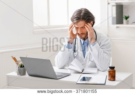 Professional Burnout. Tired Male Doctor Suffering From Headache At Workplace, Free Space
