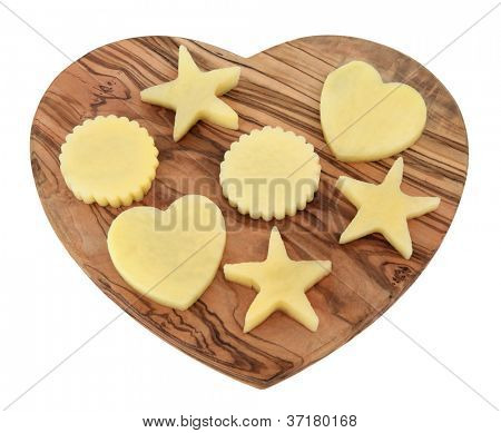 Raw potato shapes of star, heart and serrated circle on an olive wood board isolated over white background.