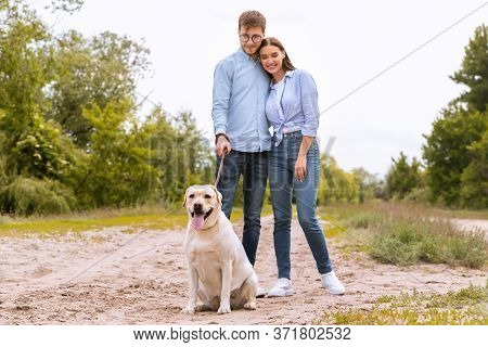 Casual Lifestyle Concept. Lovely Couple Taking Their Obedient Labrador For A Walk Outdoors, Standing