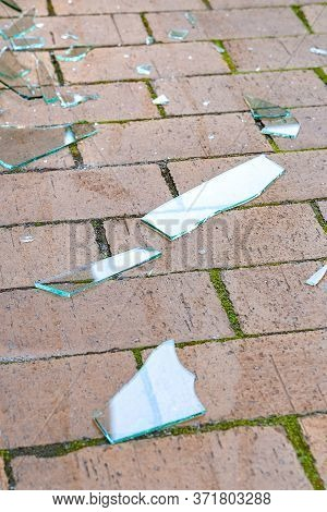 Broken Glass. Pieces Of Broken Glass On The Paving Stones. The Concept Of Destruction. Image For Edi