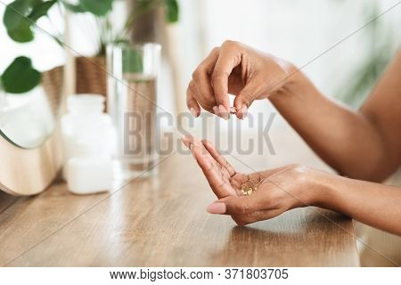 Unrecognizable African Woman Taking Beauty Supplements For Glowing Skin, Holding Omega-3 Fish Oil Ca