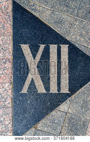 Sign On The Cobblestones In The Form Of A Roman Numeral Twelve. Street Paving. Cobblestone Pavement.