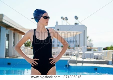 Portrait Of Teenage Girl Swimmer Wearing Swim Goggles Swimming Cap, Outdoor Swimming Pool Background