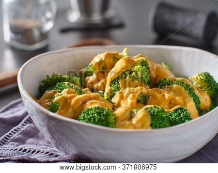steamed broccoli with melted cheddar cheese sauce in bowl