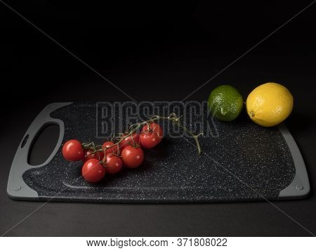 Cherry Tomatoes, Lemon And Lime On A Black Background.