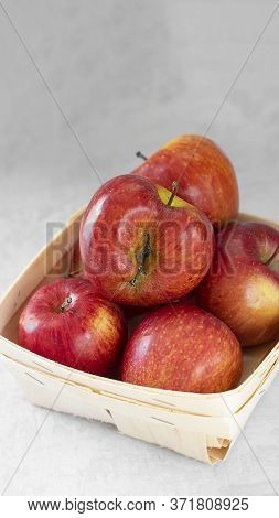 Red Fresh Organic Apples In Small Wooden Pottle With Ugly Fruit On Top. On Grey Cement Background. B
