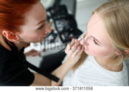Makeup Artist Does Makeup Face To Blonde Girl. Microblading Or Hardware Method Eyebrow Tattooing. Av