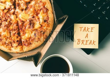 Pizza In Box, Cup Of Coffee, Laptop And Sticker With Text Take A Break On Desk In Office. Concept Of