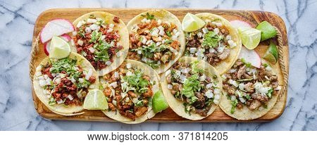wooden tray full of mexican street tacos