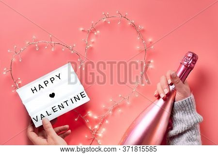 Valentine Flat Lay, Top View On Pink Background. Hands Holding Lightbox With Text Happy Valentine An