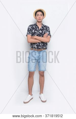 full length Summer man wearing new stylish floral, plant ,leaves fern printed short shirts with hat , blue jeans shorts and white and white sneaker, shoes with arms crossed on white background