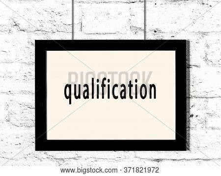 Black Wooden Frame With Inscription Qualification Hanging On White Brick Wall
