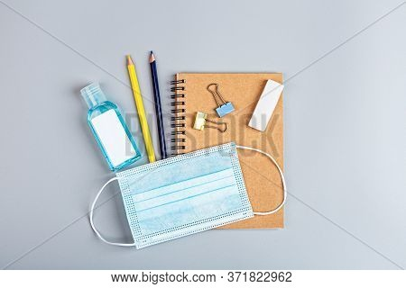 School Supplies With Medical Face Mask On A Gray Background. Protection Of Schoolchildren And Studen