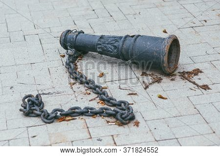 An Old Antique Rusty, Metal Balustrade Baluster With A Heavy Chain Lying On A Tile In A Park