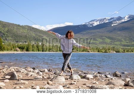 Portrait Of A Beautiful Young Woman Resting On The Shore Of A Mountain Lake On A Leafy Day. Pretty G