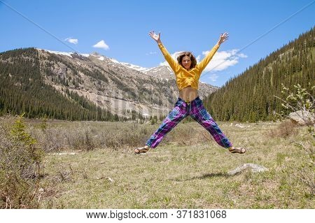 Woman Jumping For Joy. Beautiful Young Brunette Woman Enjoys A Beautiful Mountain Landscape While Tr